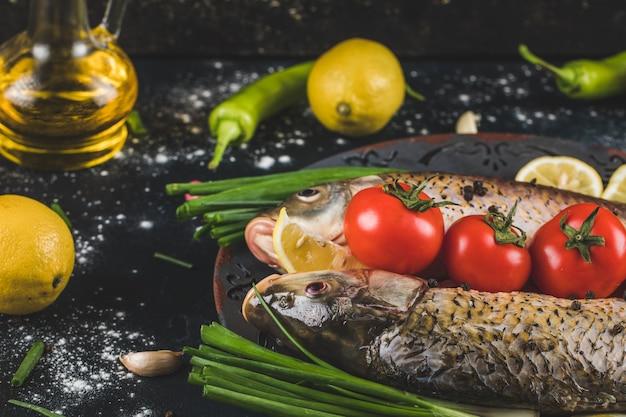 Pesce crudo pronto per la cottura con erbe, spezie, pomodori e limone in un piatto decorativo