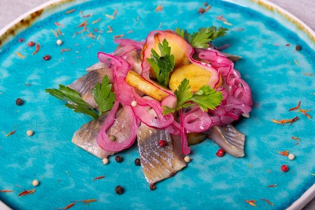 Pesce di aringhe su un piatto blu con il servizio del ristorante delle patate e del prezzemolo