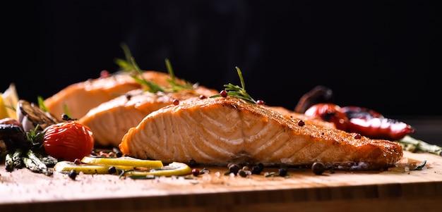 Pesce di color salmone arrostito e varie verdure sulla tavola di legno sul nero