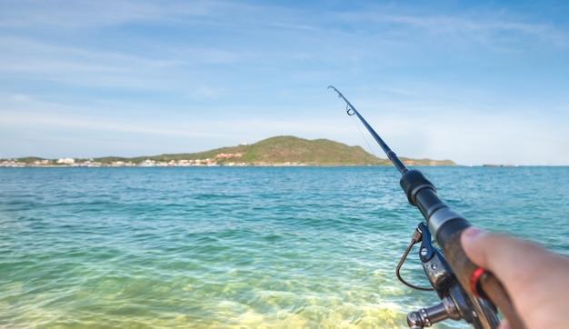 Pesce di combattimento della canna da pesca della tenuta del pescatore nel mare dell'oceano. attività sportive o pesca e acquacoltura.