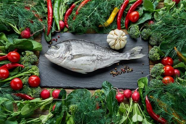 Pesce di dorada e verdure verdi intorno sulla vecchia tavola di legno. vista dall'alto, cibo sano.