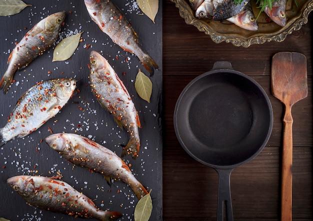 Pesce di fiume su una tavola nera e una padella nera in ghisa