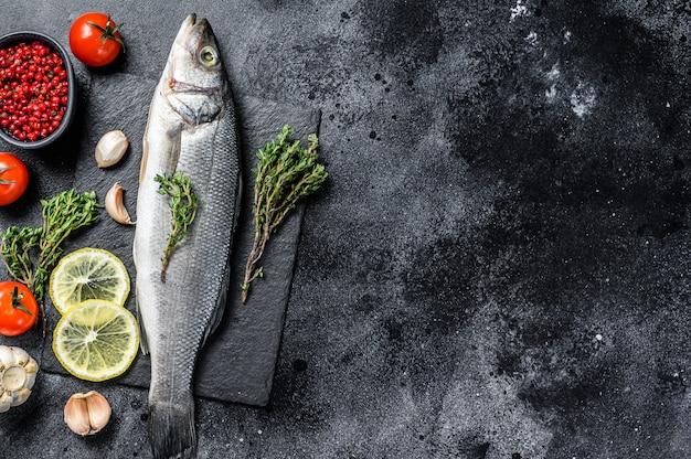Pesce di spigola con erbe e limone sul tavolo nero.