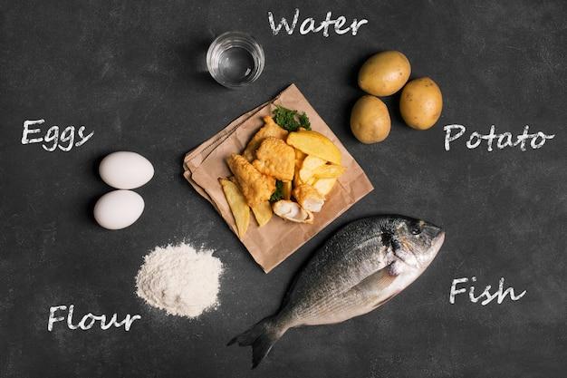 Pesce e patate fritte britannico tradizionale sulla superficie scura