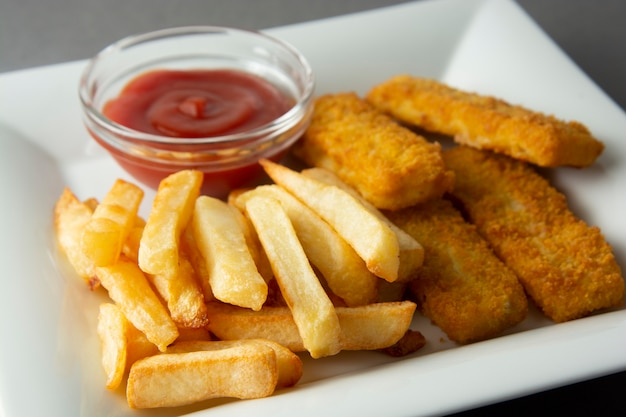 Pesce e patate fritte del primo piano con le patate fritte - alimento non sano, backgrpound grigio.