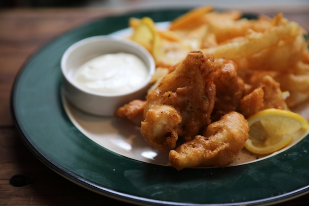 Pesce e patate fritte pesce e patate fritte su stile d'annata di legno del fondo