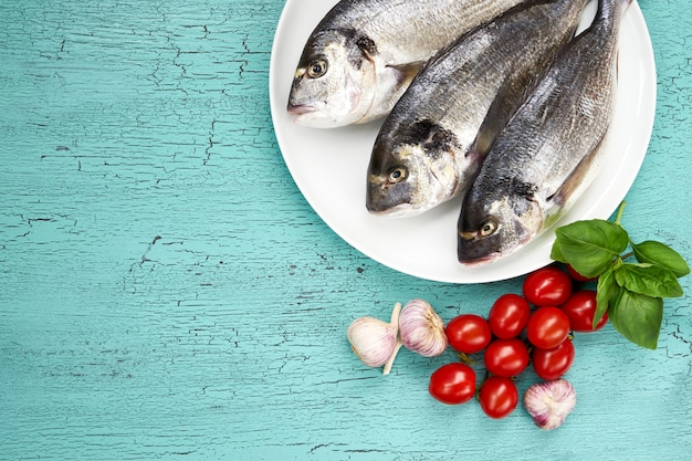 Pesce fresco crudo di dorado sul piatto e sulle verdure bianchi sulla tavola blu.
