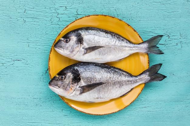 Pesce fresco crudo di dorado sul piatto giallo