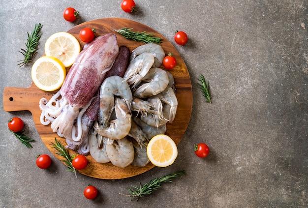 Pesce fresco crudo (gamberetti, calamari) su tavola di legno