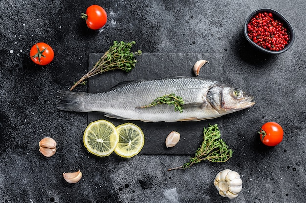 Pesce fresco del branzino con le erbe e limone su una banda nera sulla tavola nera.