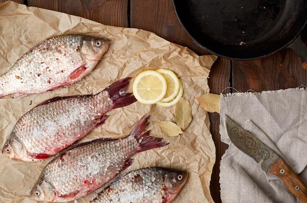 Pesce fresco di crucian con squame su un pezzo di carta marrone spiegazzato