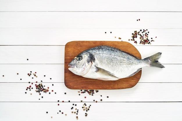Pesce fresco di dorado sul tagliere di legno con aglio.