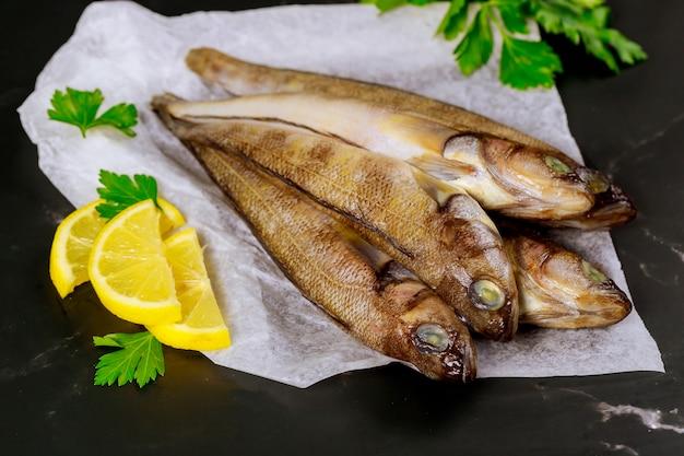 Pesce fresco intero su carta pergamena con limone e prezzemolo.