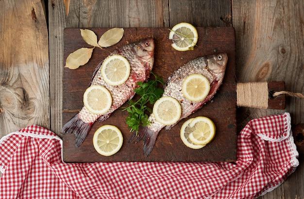 Pesce fresco nelle scale crucian su un tagliere di legno anziano marrone