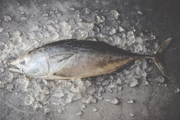 Pesce fresco su ghiaccio nel mercato - frutti di mare del pesce crudo sulla vista superiore del fondo nero, tonno di longtail, piccolo tonno orientale