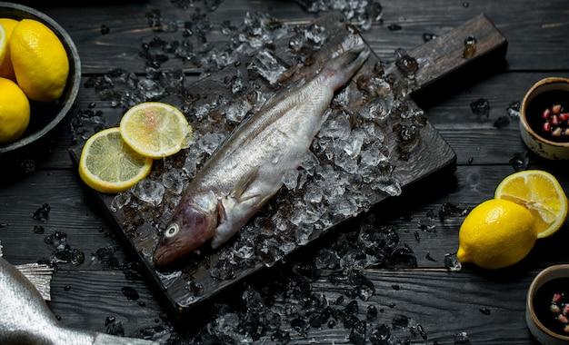 Pesce fresco su una tavola di legno con cubetti di ghiaccio e limone