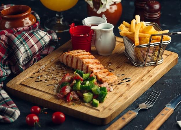 Pesce fritto con insalata e patate fritte fresche