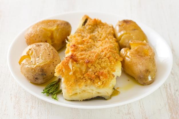 Pesce fritto con la patata e l'olio sul piatto su bianco