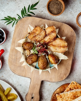 Pesce fritto con patate e cipolle al forno