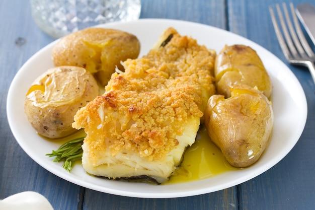 Pesce fritto con patate e olio sul piatto e bicchiere di vino