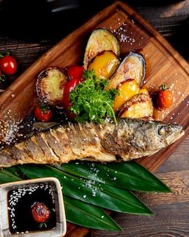 Pesce fritto con peperoni e pomodori grigliati delle melanzane