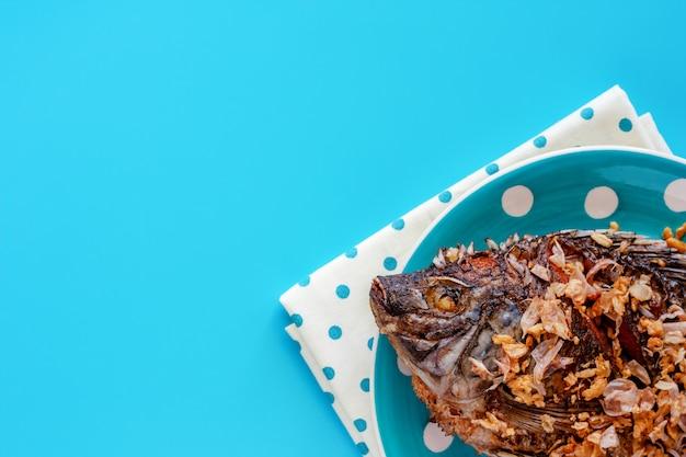 Pesce fritto delizioso di tilapia nel piatto del punto di polka su fondo blu