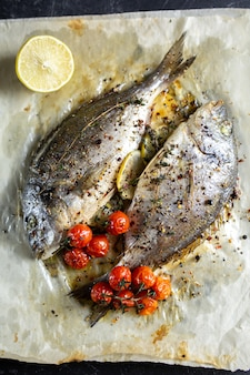 Pesce fritto di dorado su carta con il limone, i rosmarini ed i pomodori su un fondo grigio, vista superiore. pesce arrostito di dorado su un piatto di pietra.