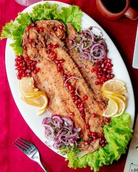 Pesce fritto servito con fette di cipolla e limone di lattuga al melograno