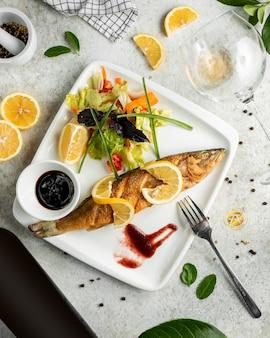 Pesce fritto servito con insalata fresca, limone e narsharab