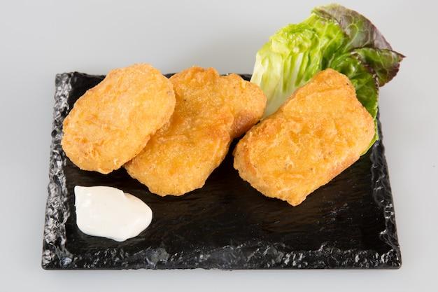 Pesce fritto su un'ardesia nera con insalata