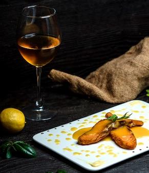 Pesce fritto versato con salsa al limone e un bicchiere di champagne