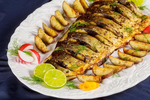 Pesce grigliato al forno con patate e verdure arrosto