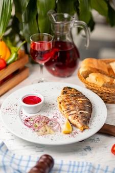 Pesce grigliato arrosto servito con erbe, limone, insalata di cipolle e salsa di pomodoro rosso.