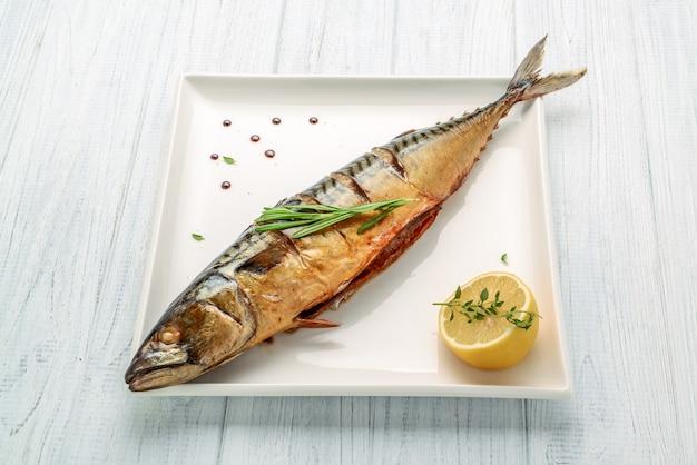 Pesce intero al forno grigliato su un piatto con verdure e limone