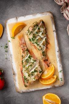 Pesce intero alla griglia con prezzemolo e arancia