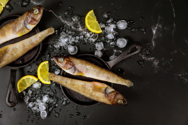 Pesce intero crudo con ghiaccio e limone sulla tavola nera.