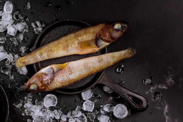 Pesce intero crudo con ghiaccio sulla tavola nera.