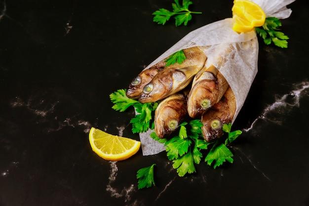 Pesce intero crudo con prezzemolo e limone avvolti in carta pergamena sul tavolo nero.