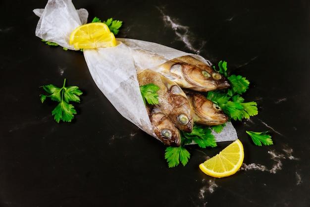 Pesce intero crudo con prezzemolo e limone avvolti in carta pergamena sulla tavola nera.