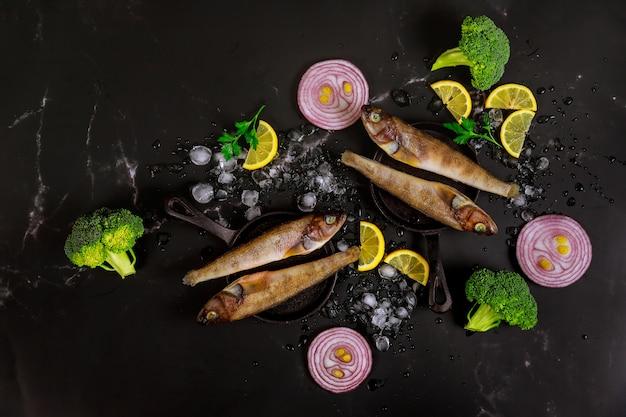 Pesce intero fresco con ghiaccio, prezzemolo e limone sulla tavola nera.