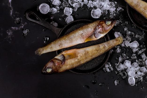 Pesce intero fresco con ghiaccio sulla tavola nera.
