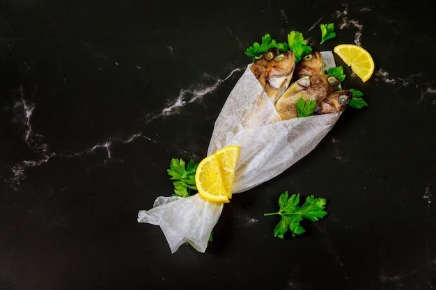 Pesce intero fresco con prezzemolo e limone avvolti in carta pergamena sulla tavola nera.