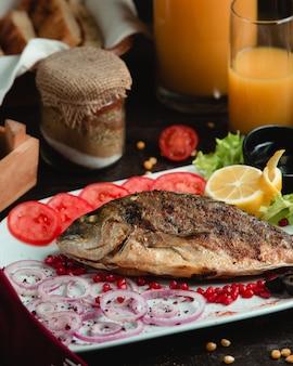 Pesce intero grigliato e servito con pomodoro, limone e cipolla.