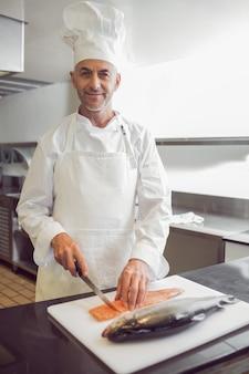 Pesce maschio sorridente di taglio del cuoco unico in cucina
