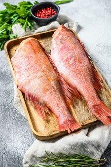 Pesce persico crudo in una ciotola di legno con prezzemolo