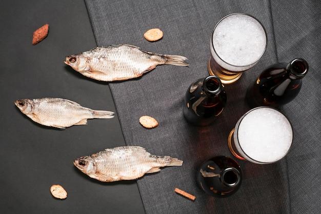 Pesce piatto disteso con bicchieri di birra e bottiglie