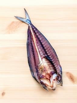 Pesce salato conservato sul tagliere di legno.