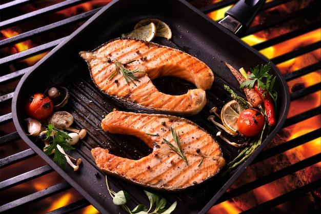 Pesce salmone alla griglia con verdure varie in padella sulla griglia fiammeggiante