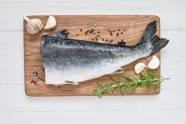 Pesce salmone crudo con rosmarino e aglio sul tagliere. vista dall'alto, copia spazio