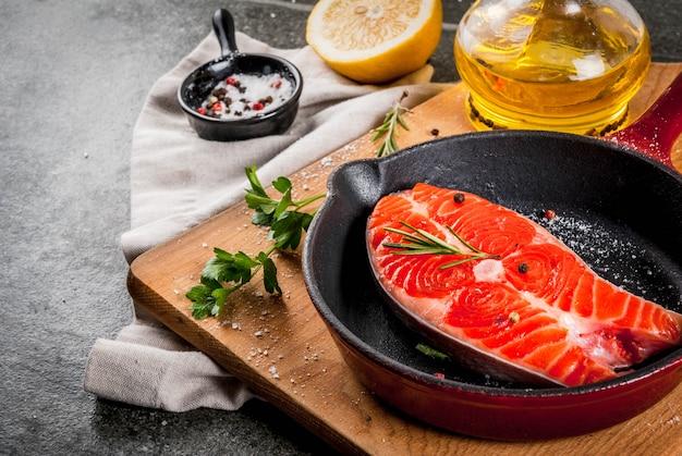 Pesce salmone fresco crudo con ingredienti per cucinare - olio d'oliva, limone, cipolla, prezzemolo, rosmarino, su padella, tavolo in pietra nera, copyspace